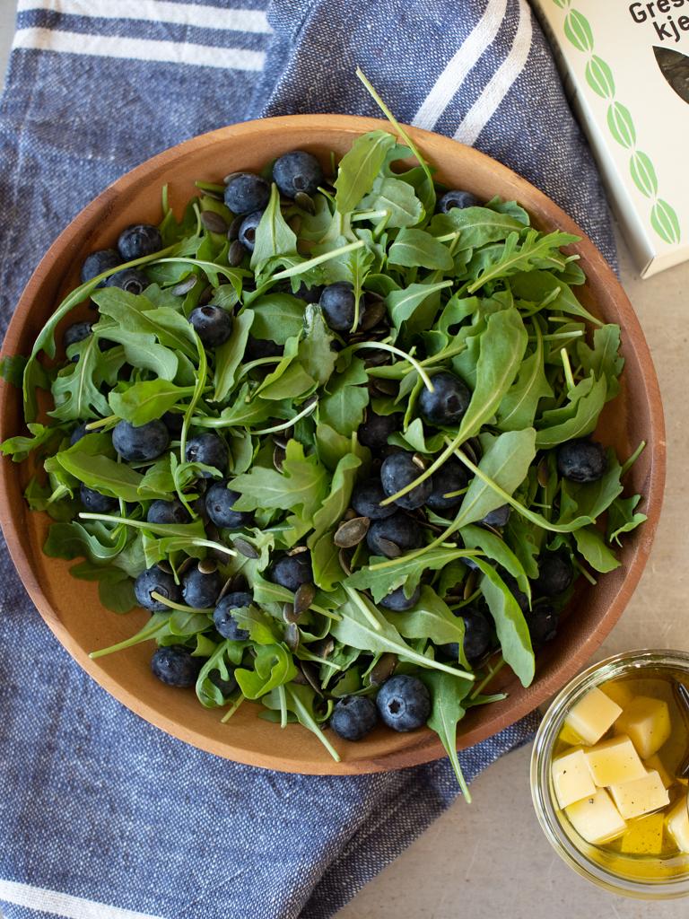 Ruccolasalat med blåbær, ost og graskarkjerner